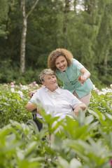Senior woman and nurse in a garden