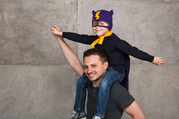 Father and son posing on gray background