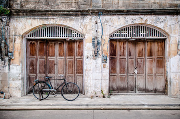 Old wooden door, rustic concrete wall and vintage bike.