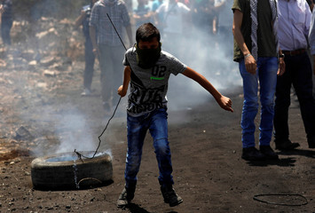 A Palestinian protester pulls a tyre during clashes with Israeli troops following a protest against the nearby Jewish settlement of Qadomem, in the West Bank village of Kofr Qadom, near Nablus