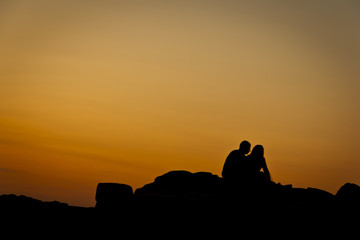 Silhouettes of a couple sitting to each other