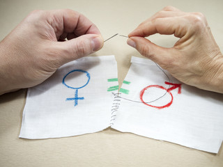 The hands of a man and a woman sewing the symbol of gender equality