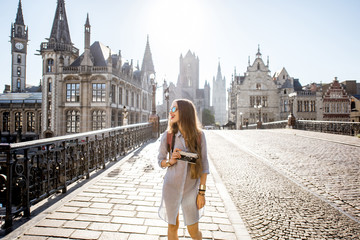 Young woman tourist walking the bridge in the old town of Gent city durnig the sunrise in Belgium