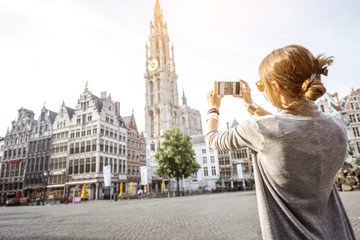 Young woman tourist photographing with phone famous cathedral standing on the Great Market square during the morning in Antwerpen, Belgium