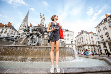 Young woman tourist with photo camera and red bag standing near the fountain on the Royal square in Nantes city, France Fotomurales