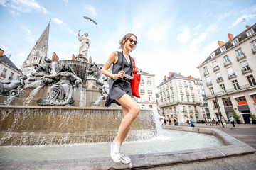 Young woman tourist with photo camera and red bag having fun near the fountain on the Royal square in Nantes city, France