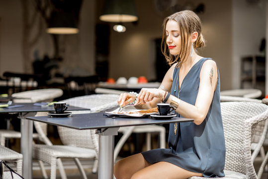 Young woman having a breakfast with french pancakes called galette sitting at the restaurant outdoors in Nantes city