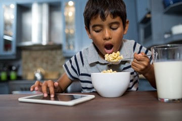 Close up of boy using tablet computer while having breakfast