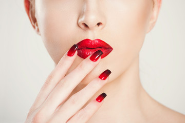 Make up and manicure set. macro cropped image of beautiful gradient of red black manicure and lipstick isolated on white background.
