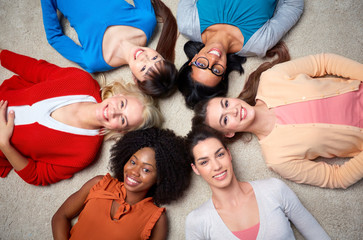 international group of happy women lying on floor
