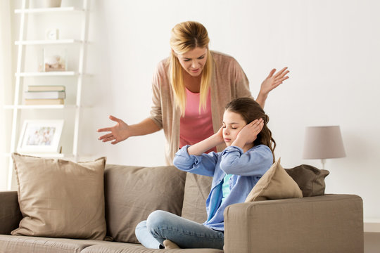 girl closing ears to not hear angry mother at home
