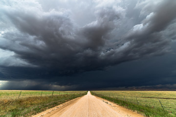 Door stickers Storm Dirt road with dark storm clouds