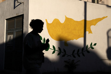 A woman is silhouetted as she walks past a Cypriot flag painted on a wall in Nicosia