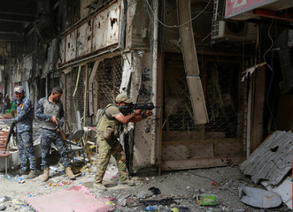 A member of the Emergency Response Division opens fire against Islamic State militants in the Old City of Mosul