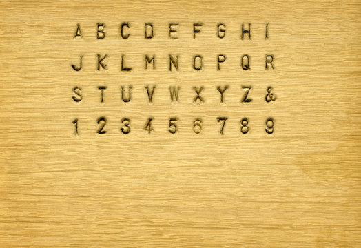 Punched on wood alphabet with background texture for composing your message