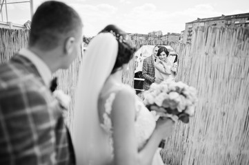 Fantastic bride and handsome groom looking in the mirror on their wedding day. Black and white photo.