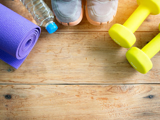 Dumbbells,sport sneakers, bottle of water and yoga mat for fitness.