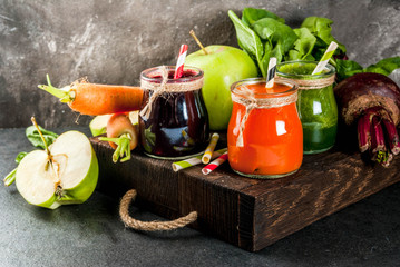 Vegan diet food. Detox drinks. Freshly squeezed juices and smoothies from vegetables: beets, carrots, spinach, cucumber, apple. On dark stone background, wooden tray, ingredients. Copy space