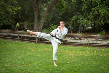 Young man in karate gi demonstrates a high kick in a public park