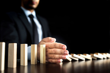 Businessman Letting Or Preventing  Dominoes Chain Toppling