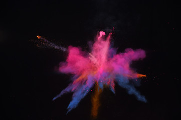 Bizarre forms of red powder paint exploding in front of a black background to give off fantastic colors and forms.