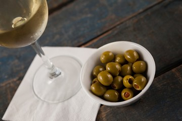 Cropped image of wineglass by green olives served in container