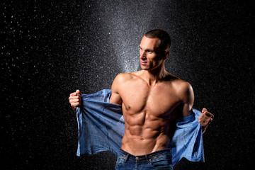 wet fitness muscular male model standing on rain