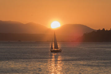 Sailing under the sun near Seattle with Olympic mountains on the Salish sea at sunset