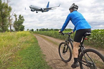 cyclist riding along a trail on the background of flying a passenger jet.