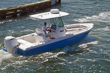 A small open sport fishing boat powered by a single outboard engine cruising the florida intra-coastal waterway near Miami Beach.