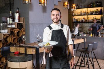A handsome young guy with a beard dressed in an apron standing in a restaurant and holding a white plate with a moth. Against the background, the bar counter and loft style interior