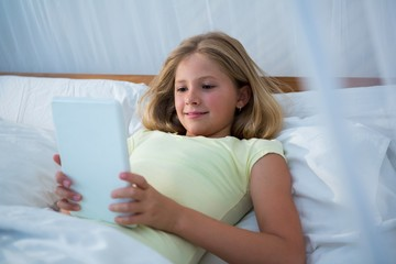 Girl using tablet while lying on bed