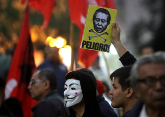 A protester holds a sign with an image of former president Alberto Fujimori with the word 'Danger' during a march against a possible pardon for Fujimori, who has been serving a 25-year sentence for human rights violations, in Lima, Peru