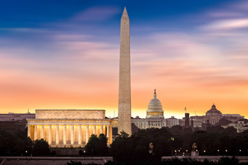 Dawn over Washington - with 3 iconic monuments illuminated at sunrise: Lincoln Memorial, Washington Monument and the Capitol Building.