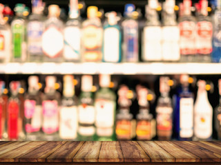 Empty top of wooden table with blurred counter bar and bottles Background.