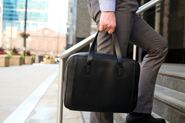 Businessman walking and holding  a  leather briefcase in his handss Modern city behind
