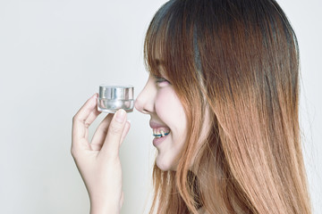 Asian woman holding whitening cream bottles