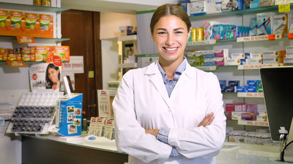 Portrait of a beautiful young girl (woman) pharmacist, consultant, working at a pharmacy, selling and checking medication, smiling, giving advice. Concept: profession, medecine, medical education.