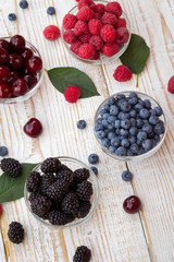 Raspberries, blackberries, cherries and blueberries in a glass bowls