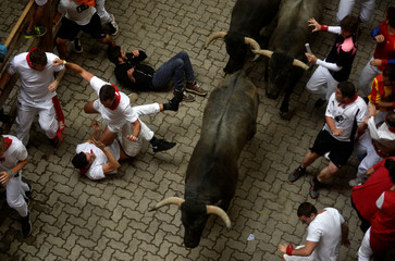 A runner falls in front of Jose Escolar Gil bulls during the second running of the bulls at the San Fermin festival in Pamplona
