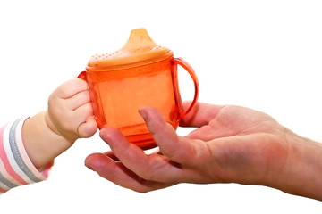 The hand of the baby gives a drinker to an adult