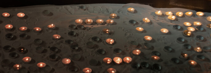 Many small votive candles on a sand in a special holder box
