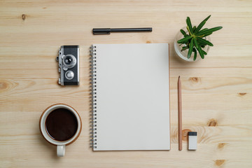 Top view workspace mockup on wood table with notebook, pen, coffee, clips and accessories.
