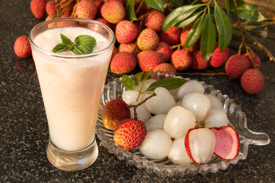 Litchi juice in a glass. Fresh juicy lychee fruit on a glass plate.