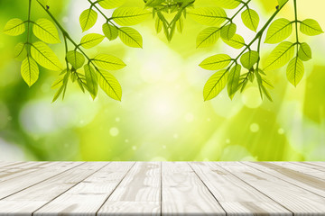 Wood table and Green leaves hanging with green blurred backgrounds.