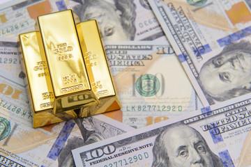 Three gold bar with hundred dollar bills