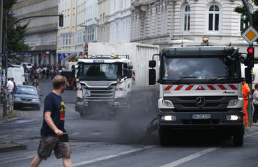 Workers clean a street from burned down barricades after demonstrations at the G20 summit in Hamburg