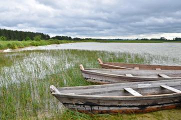 Old rustic wooden fishing boats on the lake at stormy weather, close up