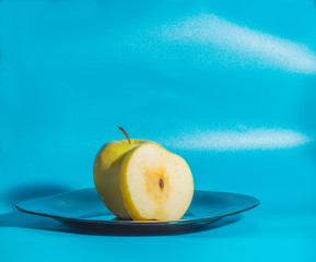 on a blue background yellow Apple in the plate.