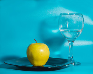 on a blue background yellow Apple in the plate with a glass of water.